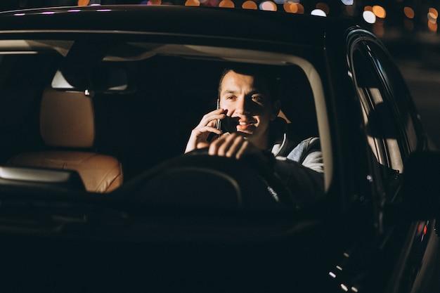 Homme conduisant une voiture sur la route et parlant au téléphone Photo gratuit