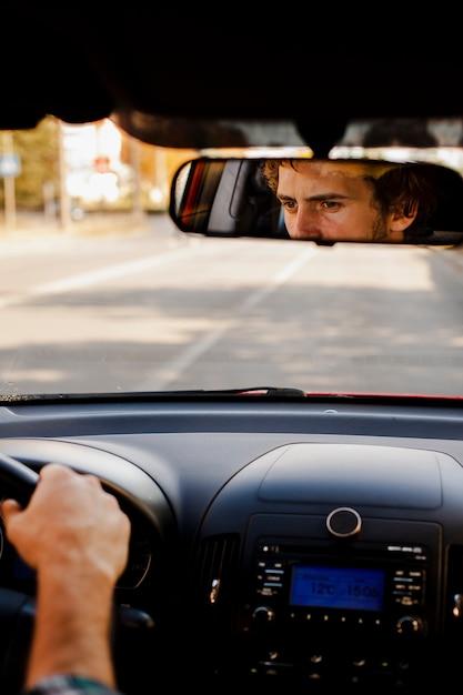 Homme conduisant une voiture vue à travers le rétroviseur Photo gratuit