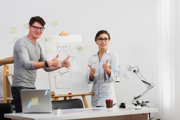 Homme confiant et femme montrant un signe ok à côté d'un diagramme Photo gratuit