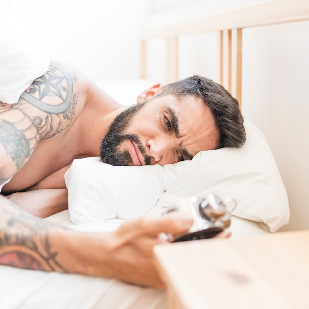 Homme contrarié allongé sur un lit en regardant réveil Photo gratuit