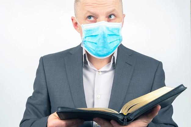 L'homme En Costume D'affaires Avec Un Masque Médical Sur Son Visage étudie La Bible. Photo Premium