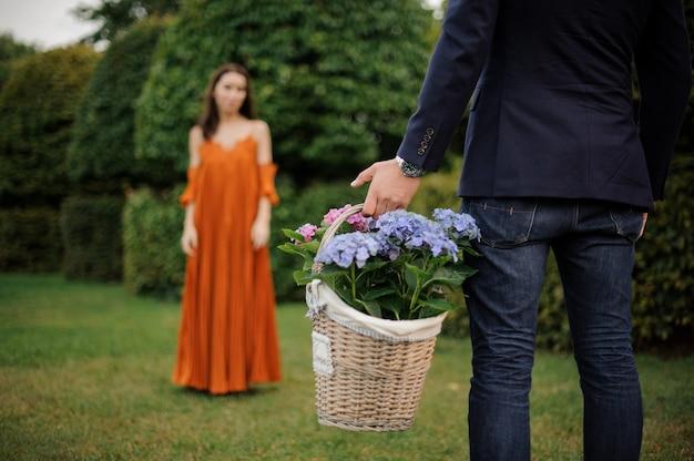 Homme en costume apporte un grand panier en osier rempli de fleurs pour une femme Photo Premium