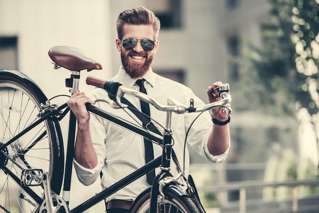 Homme en costume classique et lunettes de soleil porte son vélo. Photo Premium