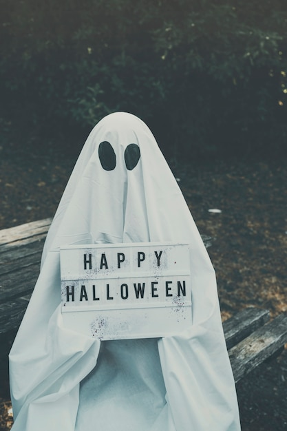 Homme en costume fantôme assis sur un banc et tenant une tablette Photo gratuit
