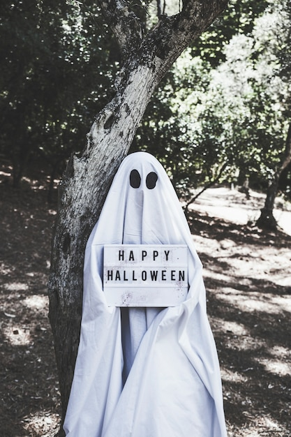 Homme en costume de fantôme près de l'arbre dans la forêt tenant la tablette d'halloween Photo gratuit
