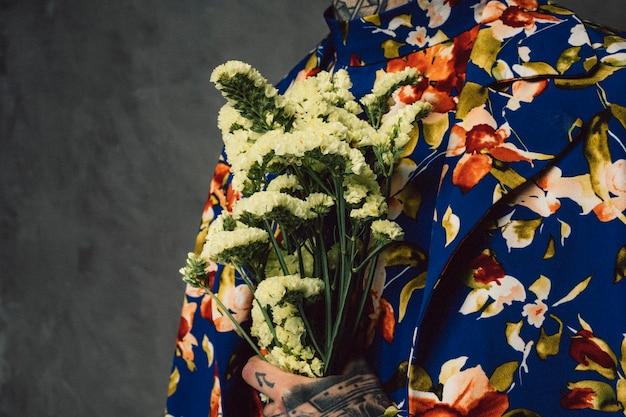Homme en costume floral tenant une fleur de limonium jaune à la main Photo gratuit