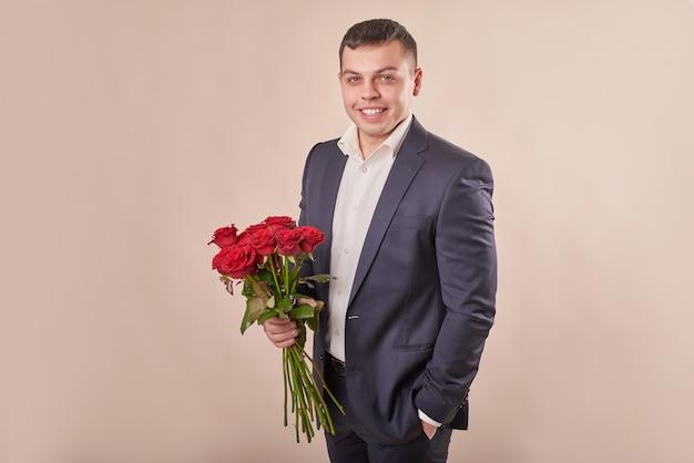 Homme En Costume Gris Avec Roses Rouges Photo Premium