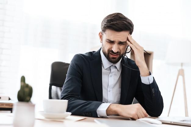 Un homme en costume a mal à la tête. il garde ses mains. Photo Premium