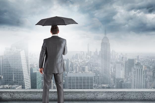 Homme en costume et parapluie regardant la ville Photo gratuit