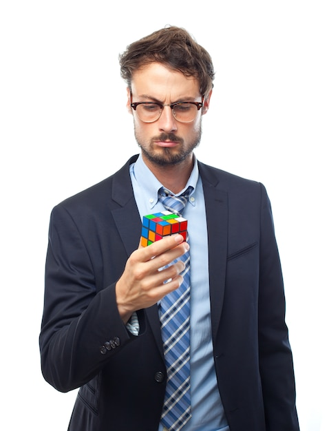 L'homme avec le costume regardant un cube de rubik Photo gratuit