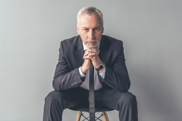 Homme en costume regarde la caméra assis sur une chaise. Photo Premium
