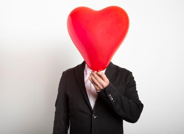 Homme En Costume Se Cachant Derrière Un Ballon En Forme De Coeur Rouge. Homme Tenant Le Symbole De L'amour, De La Famille, De L'espoir. Photo Premium