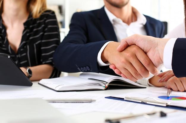 Homme en costume serrer la main comme bonjour au bureau closeup Photo Premium
