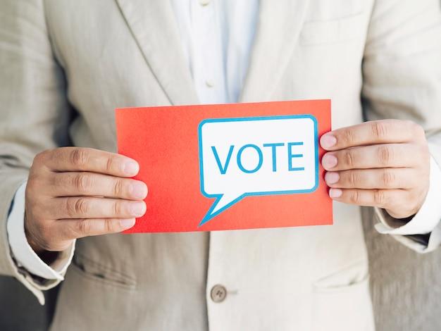 Homme en costume tenant un message de vote Photo gratuit