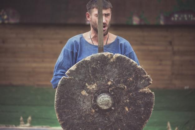 Un homme en costume de viking tient une épée et un bouclier Photo Premium