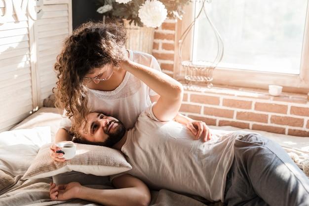 Homme couché sur les genoux d'une femme tenant une tasse de café dans la main se regardant Photo gratuit