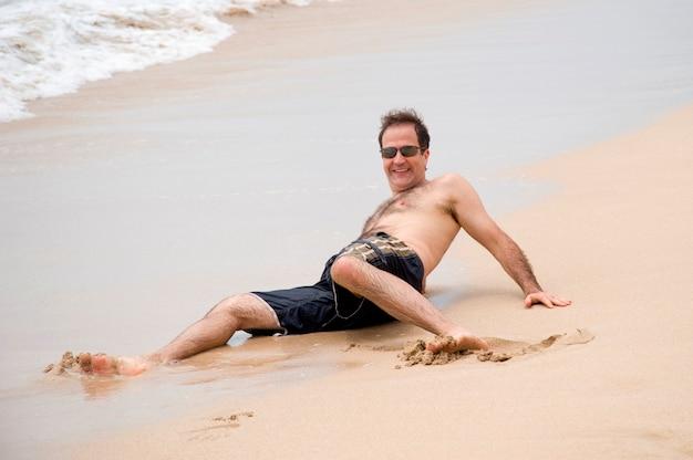 Homme couché sur le sable le long du rivage à bali Photo Premium