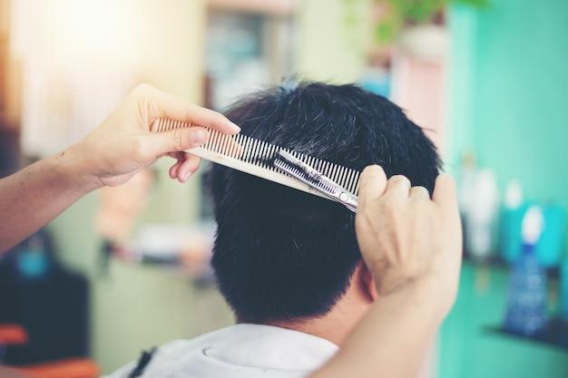 Un homme coupe les cheveux chez le coiffeur Photo Premium