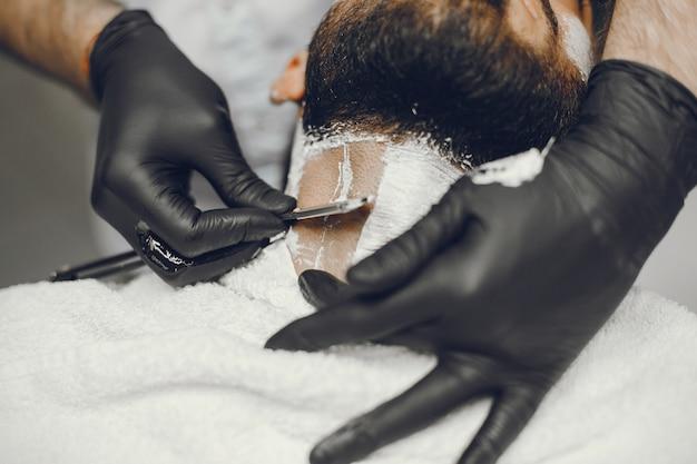 L'homme coupe sa barbe dans le salon de coiffure. Photo gratuit