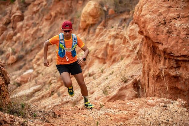 Un homme coureur de trail. et pieds d'athlètes portant des chaussures de sport pour le trail running en montagne Photo Premium