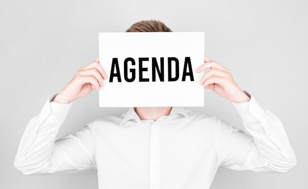 L'homme Couvre Son Visage Avec Un Livre Blanc Avec Du Texte Agenda Photo Premium