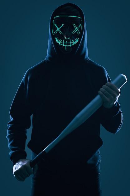 Homme Criminel Anonyme Avec Batte De Baseball Dans Un Sweat à Capuche Noir Et Un Masque De Néon Photo Premium