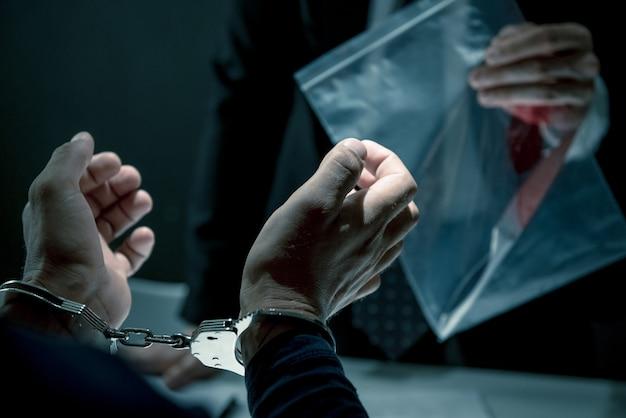 Un homme criminel avec des menottes étant interrogé dans la salle d'interrogatoire Photo Premium