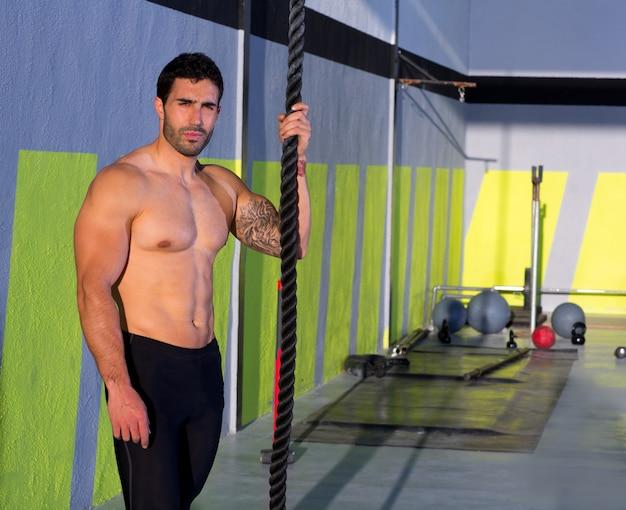 Homme crossfit avec corde d'escalade détendu au gymnase Photo Premium