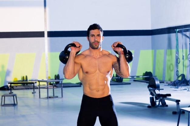 Homme crossfit soulevant un exercice d'entraînement avec kettlebell Photo Premium