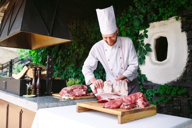 Un Homme Cuisinier Coupe La Viande Avec Un Couteau Dans Un Restaurant. Photo Premium