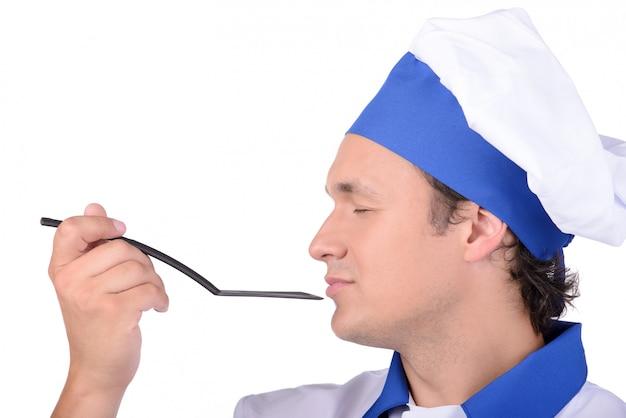 Homme cuisinier délicieusement sentir le contenu de la cuillère. Photo Premium