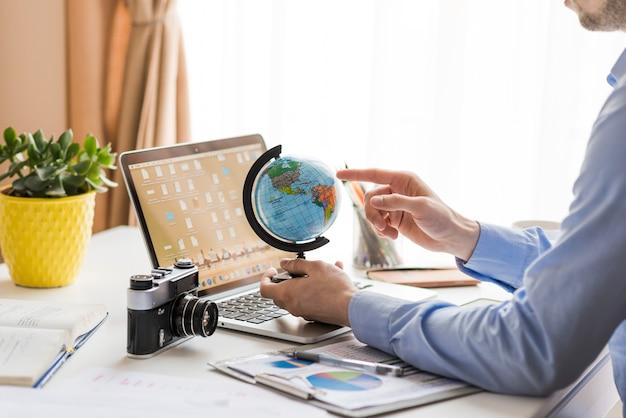 Homme de culture pointant sur globe dans le bureau Photo gratuit