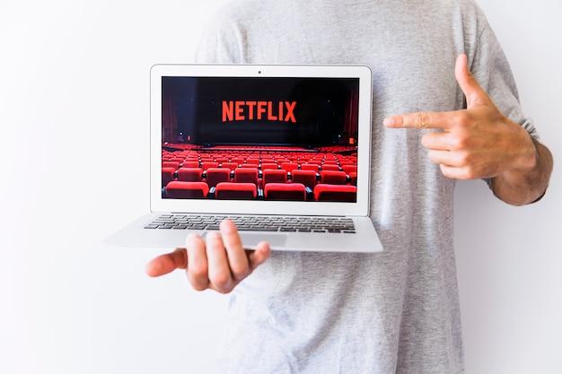 Homme de culture pointant sur l'image avec le logo netflic Photo gratuit