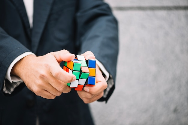 Homme de culture résolvant le cube de rubik Photo gratuit