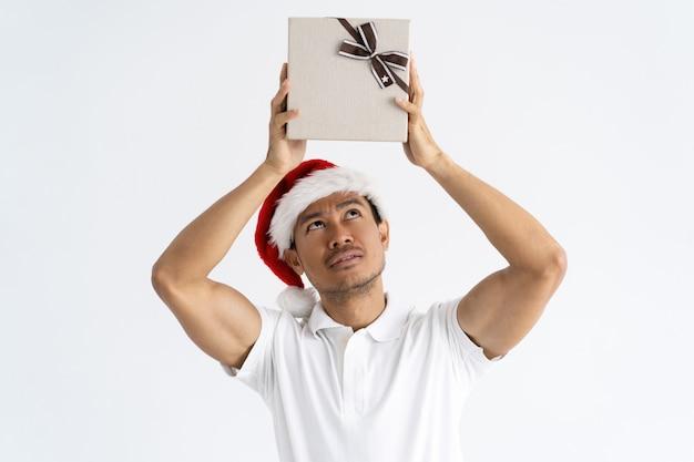 Homme curieux, porter, santa hat, et, monter, boîte cadeau, sur, tête Photo gratuit