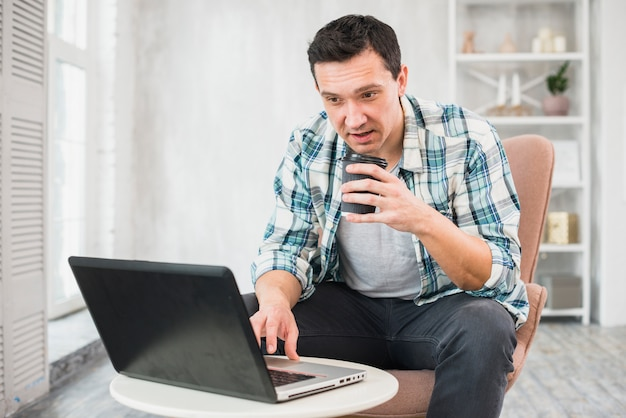 Homme, dactylographie, ordinateur portable, tenue, tasse, boisson, chaise Photo gratuit