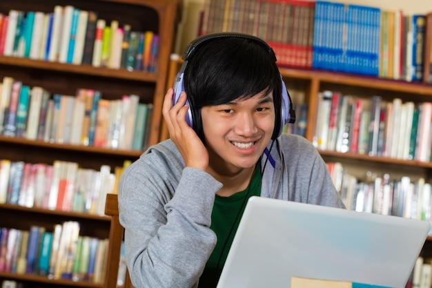 Homme dans la bibliothèque avec un ordinateur portable et des écouteurs Photo Premium