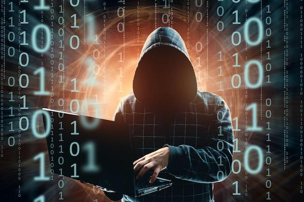 Un homme dans un capot, un pirate informatique, une attaque de pirate informatique, une silhouette d'homme, tient un ordinateur portable, menace Photo Premium