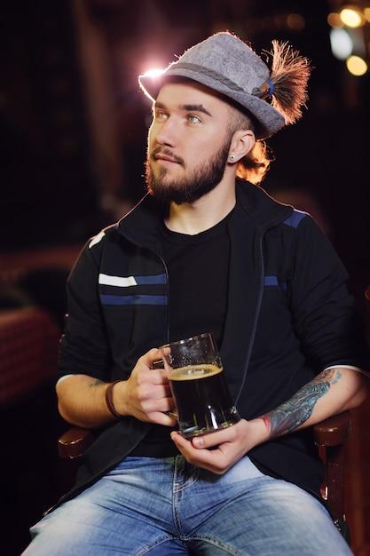 Un homme dans un chapeau bavarois buvant de la bière dans un pub et regardant le football Photo Premium