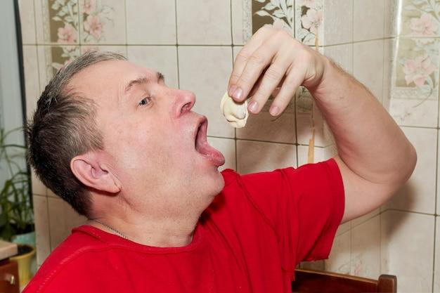 Un Homme Dans La Cuisine Se Met Une Boulette Avec Sa Main Dans Une Bouche Grande Ouverte Photo Premium