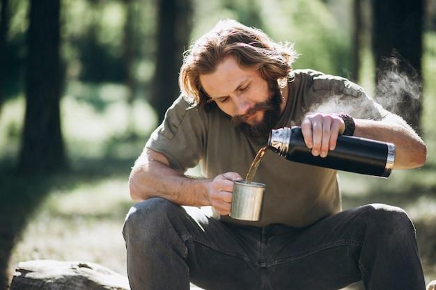 Homme dans la forêt avec du thé au feu Photo gratuit