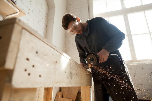 Homme dans des lunettes de protection en utilisant un moulin à angle pour couper du métal Photo gratuit