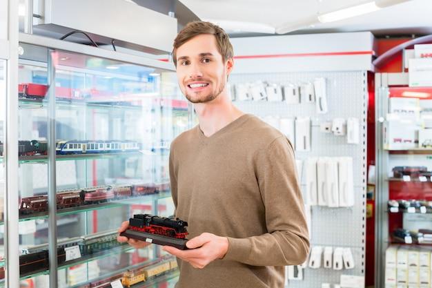 Homme dans le magasin de jouets acheter modèle de chemin de fer Photo Premium