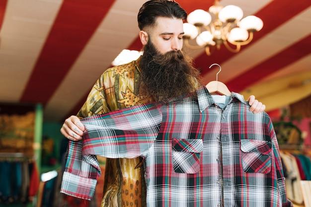 Homme dans un magasin à la mode en vérifiant chemise à carreaux Photo gratuit