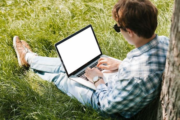Homme dans le parc travaillant sur un ordinateur portable Photo gratuit