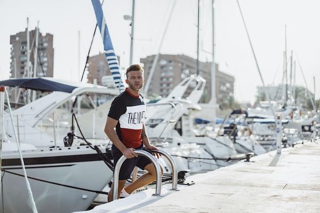 Un homme dans le port prépare le yacht pour le voyage Photo gratuit