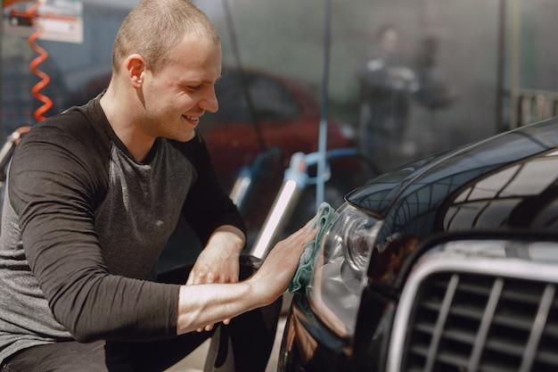 Homme Dans Un Pull Gris Essuie Une Voiture Dans Un Lave-auto Photo gratuit