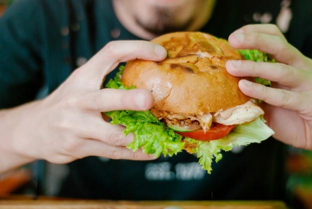 Homme dans un restaurant en train de manger un hamburger Photo Premium