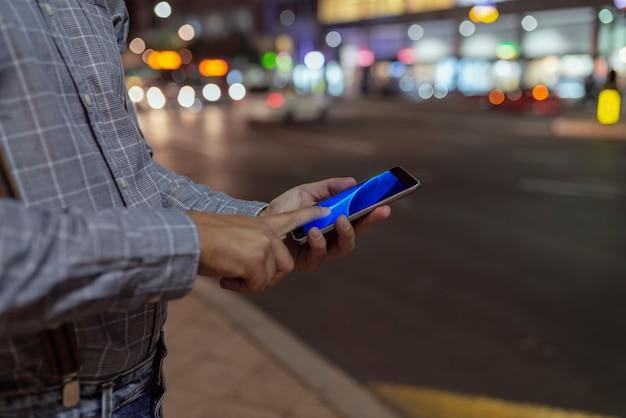 Homme Dans La Rue Avec Un Téléphone Dans Les Mains Photo Premium