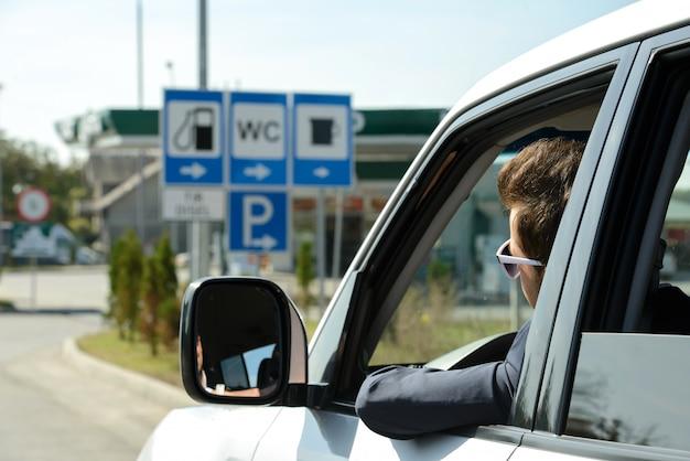 L'homme dans sa voiture s'arrête à la station d'essence. Photo Premium